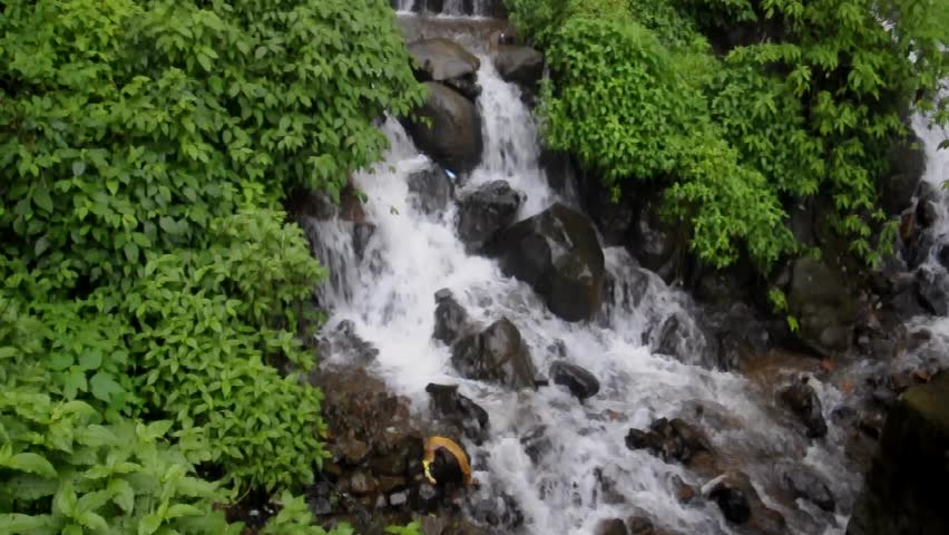 Flowing water stream or a small waterfall during rainy season in India. - HD stock video clip