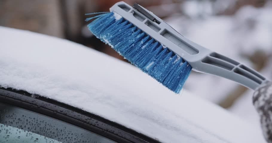Cleaning Snow and Ice off the Car's wind shield window. Slow Motion, 4K DCi. Unrecognizable man or woman brushes off the snow from the parked car. Winter snow storm, safe driving, weather challenge.