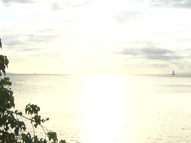 Overexposed shot of ocean with sailboats far on horizon - SD stock video clip