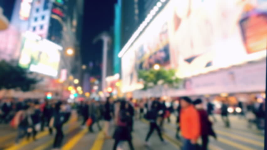 Blurred video of crowded city street with people moving at crossroad. Hong Kong night life