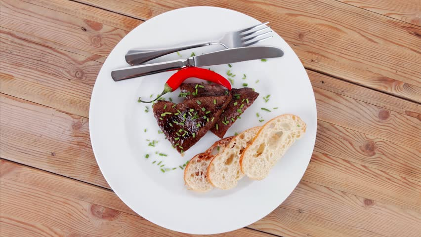 fresh hot grilled beef meat steak served with red hot pepper and white bun slices on plate over wooden table 1920x1080 intro motion slow hidef hd