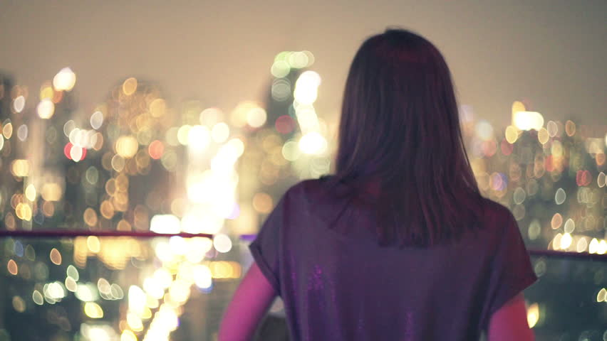 Young woman walking on terrace and admire city view during night