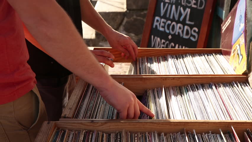 Close up of shoppers purchasing vinyl records