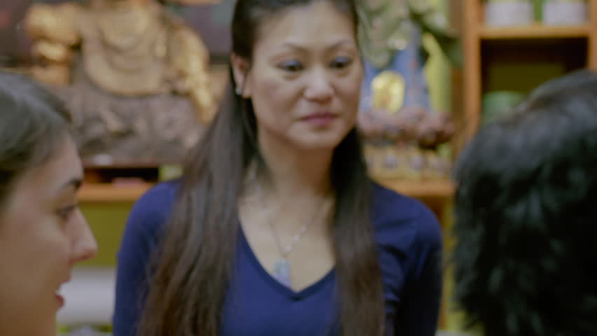 Slow motion portrait of a friendly Asian woman in a Chinese Tea House - HD stock footage clip