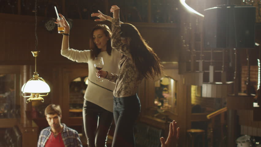 Two girls are dancing with drinks on a table while everybody are having a good time together at a bar. Shot on RED Cinema Camera. - 4K stock footage clip