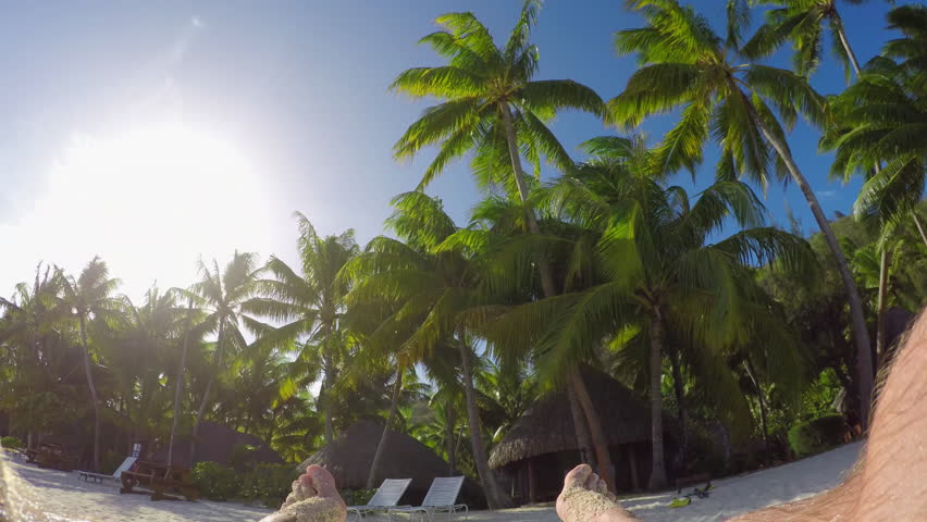 4K FPV SLOW MOTION CLOSE UP: Relaxed man enjoying vacation laying on sun lounger daybed on fantastic sunny beach with beautiful lush palm trees at luxury hotel resort with beachfront villas | Shutterstock HD Video #14483554