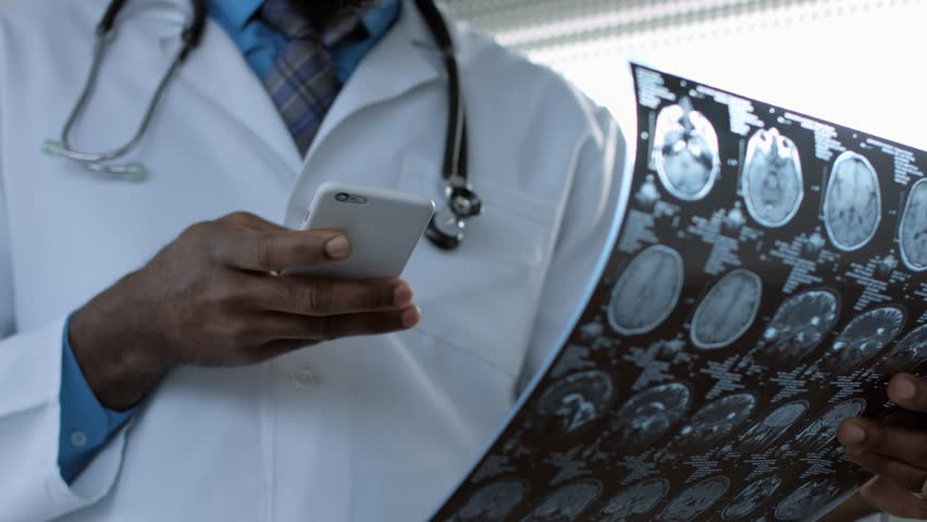 African american doctor viewing mri picture and using smart phone | Shutterstock HD Video #14616367