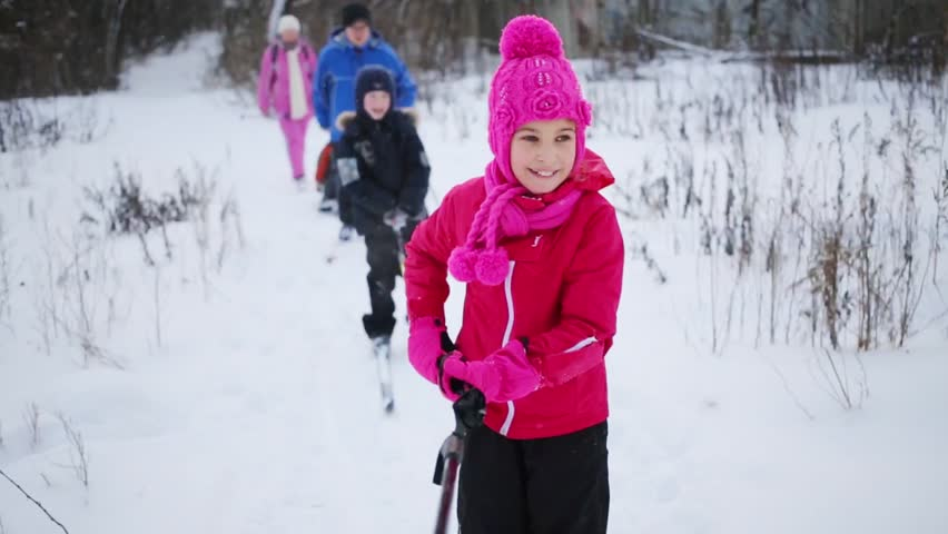 Three children and two adults rides on skis on winter day. Focus on girl. Girl keeps pole - HD stock footage clip