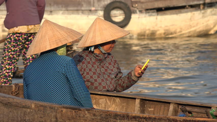 MEKONG DELTA, VIETNAM - 11 DECEMBER 2015: A Vietnamese woman wearing a traditional conical hat uses a mobile phone at the floating fruit and vegetable market nearby Can Tho