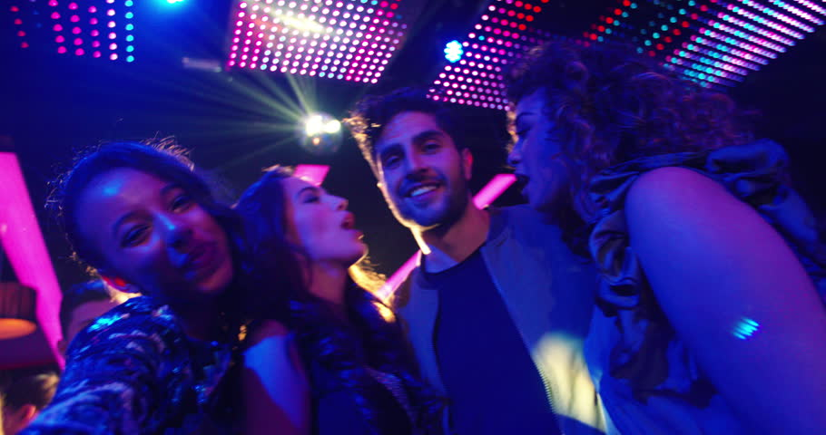Party friends with multi-ethnic decent at nightclub taking selfies and pulling faces for the photo with people, music and disco lights in the background | Shutterstock HD Video #14730856