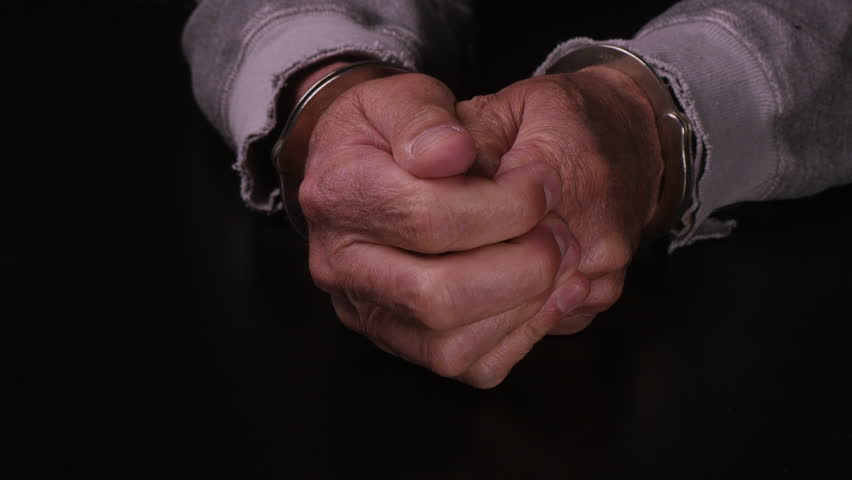 MALE HANDS IN HANDCUFFS.  PAIR OF HANDS TESTS OUT THE STRENGTH OF THE CUFFS.  CLOSE UP SHOT, ARMS IN TATTERED SWEATSHIRT ON A BLACK TABLETOP.  SHOT IN 4K.  AUDIO.