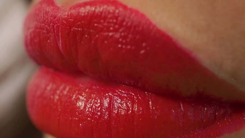 Macro video: girl with red manicure and red lips eating green grapes