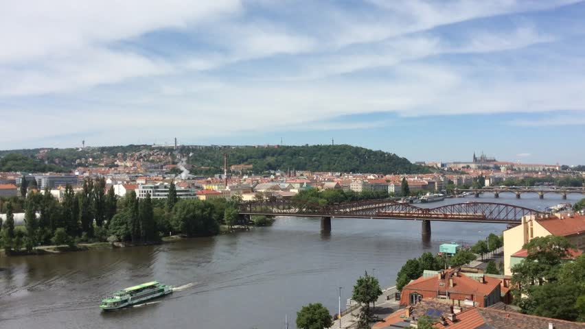 A boat is moving on the river and the tram is moving toward on the street. A river cruise is a way to see different sights of Prague. This is a view from the hill at Vysehrad fortress in Prague. | Shutterstock HD Video #14791975