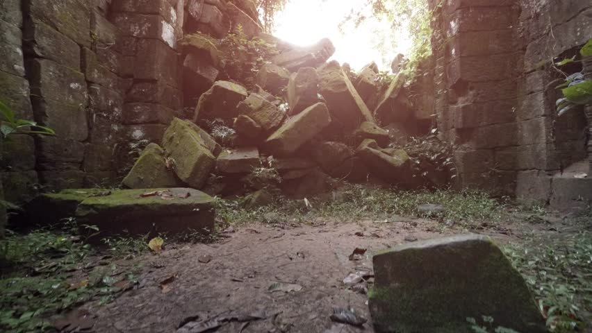 Ancient and enormous. moss covered stone blocks of a collapsed wall. overgrown with vines at a temple ruin in Cambodia. Video 3840x2160