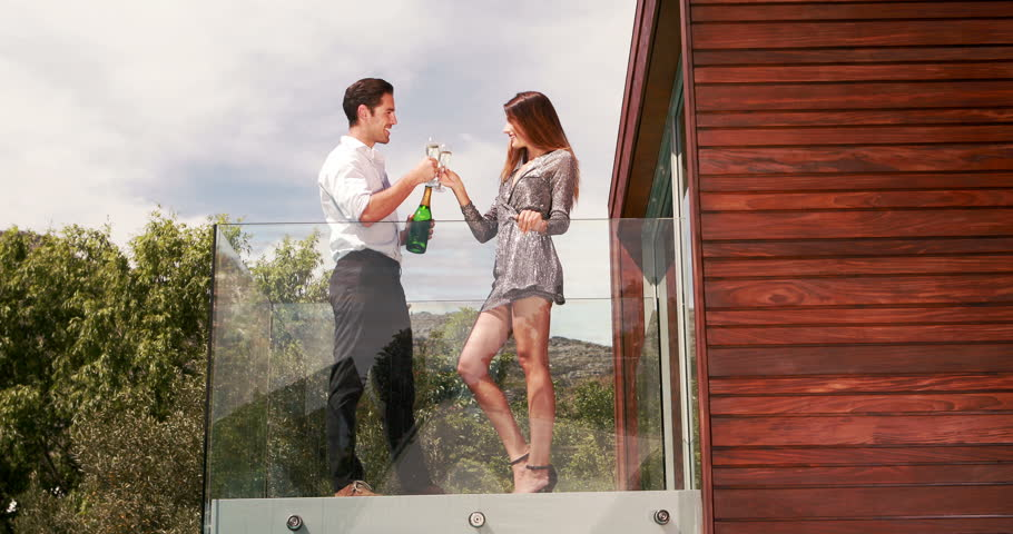 Smiling couple toasting with champagne on the balcony - 4K stock footage clip