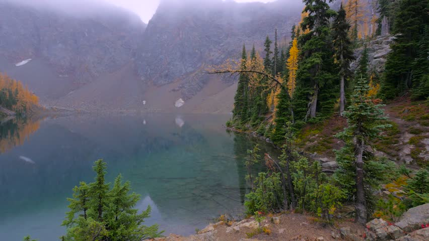 Transparent lake in the mountains. The mountains covered with green fir-trees. Forest reflection in water. Autumn.North Cascades National Park. Washington state. Landscape video.4K, high bit rate, UHD | Shutterstock HD Video #14896276