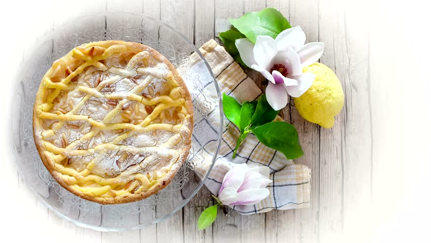 Slice of cake with ricotta, shortbread pastry and pine nuts with lemon flavor.