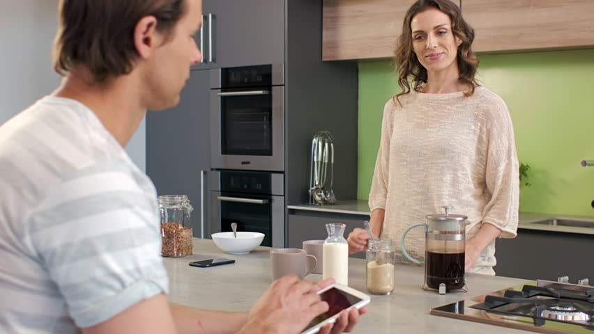 Wife hands husband a cup of coffee in the morning, breakfast routine for the married couple - HD stock video clip
