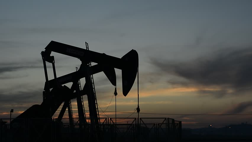 Silhouette of crude oil pump in oil field at sunset.  - HD stock video clip