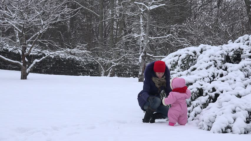 Mom with baby girl have fun in snow covered winter garden. Static shot. 4K | Shutterstock HD Video #14998273