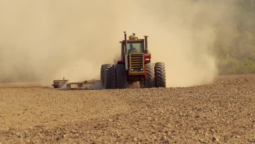 Tractor plowing field in slow motion