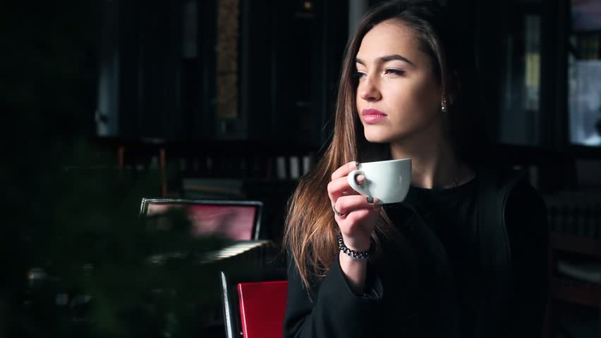 Very Beautiful Girl Drinking Coffee in a Restaurant and Smiling. | Shutterstock HD Video #15076870
