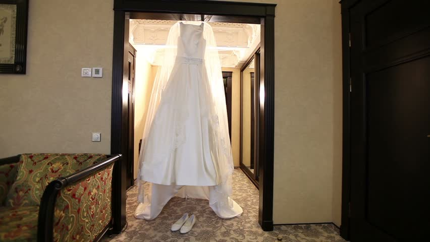 Elegant wedding dress hanging in the door, general plan, bride's shoes are in the room - HD stock footage clip