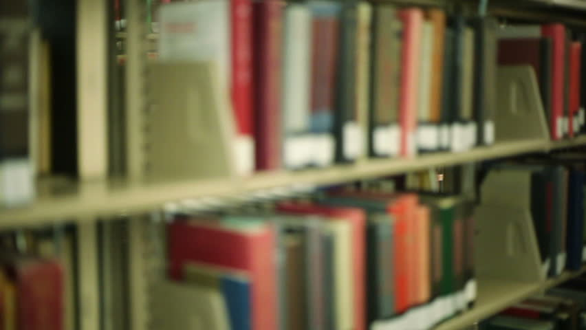 College student pulling a book off a shelf inside a library.  - HD stock footage clip