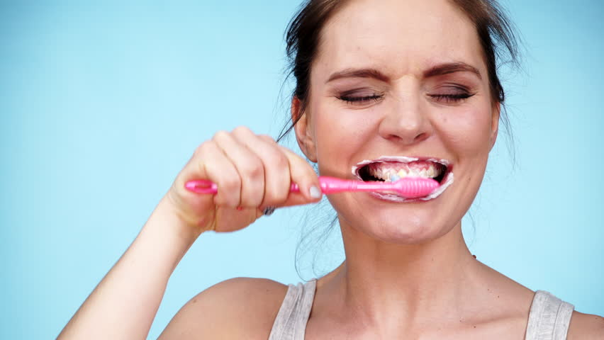 Woman brushing cleaning teeth. Girl with toothbrush. Oral hygiene. Blue background 4K ProRes HQ codec | Shutterstock HD Video #15148420