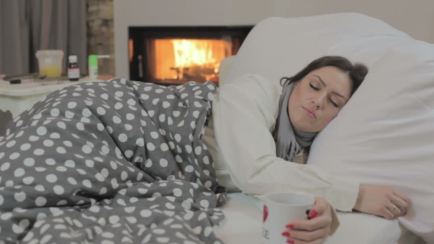 Sick young woman in bed blowing nose in paper tissue and drinking tea (medicine and fireplace in background)