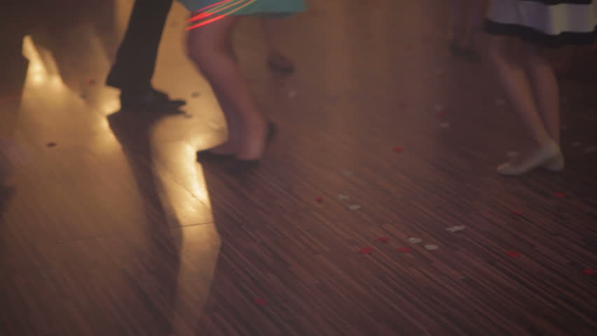 Close up of dancing women and men's feet on the dance floor at the night club or discotheque. Crowd women with beautiful legs in high heels dancing.  - HD stock footage clip