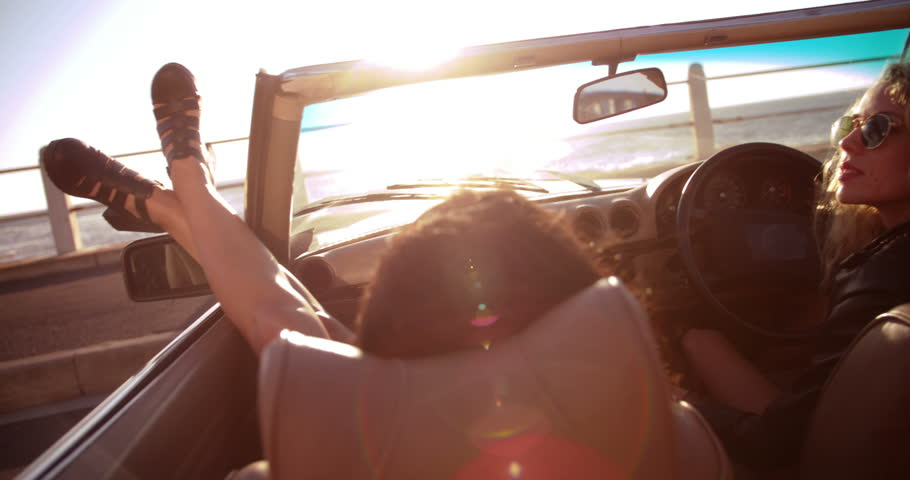 Two young women enjoying a summer sunset on seaside sitting in a vintage convertible with sunflare   Shutterstock HD Video #15173233