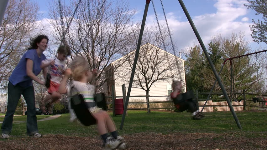 children enjoy a beautiful spring day swinging at the playground - HD stock video clip