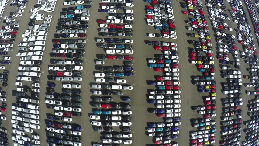 Aerial top down bird view of new car storage parking lot showing imported new vehicles or ready to export new automobiles storage facility car industrie for American and European market 4k quality