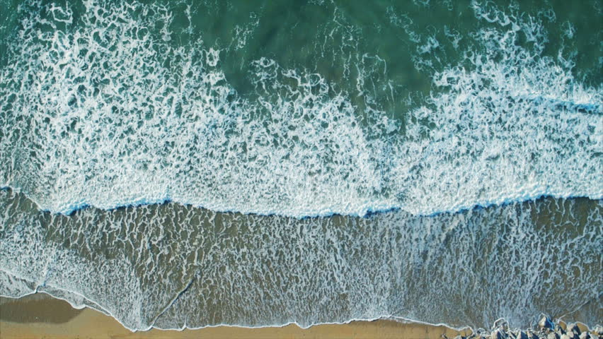 Aerial drone footage of serene sea waves reaching shore. Slow lockdown shot of textures being formed by white sea foam. As the waves calm the patterns change. Filmed from an overhead perspective. | Shutterstock HD Video #15241615