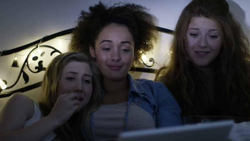 4K Young female friends having a sleepover, watching film or TV on computer