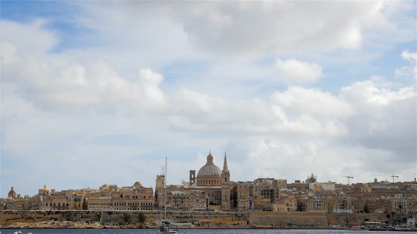 The skyline of Valletta, Malta low in the frame with the dome of the Church of St. Paul's Shipwreck dominating and a blue and white sky providing copy space. - HD stock footage clip