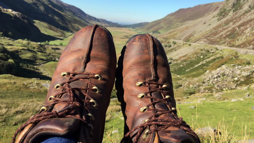 Hiker Taking A Rest Overlooking Pretty Valley. A shot of a hikers boots high up in a Welsh valley looking down to the valley floor and beyond to the sea. Shot in 4K | Shutterstock HD Video #15302167