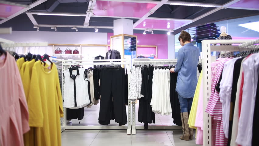 pretty elegant woman shopping in clothes store - HD stock footage clip