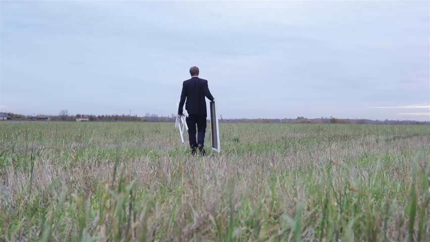 Young man in a suit with his easel and canvas walking in the summer field - HD stock video clip