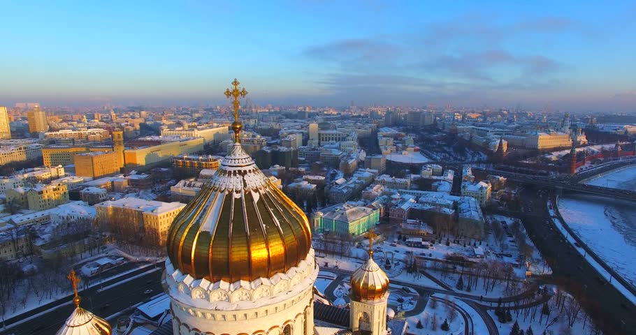 Aerial view of the dome of impressive Cathedral of Christ the Saviour and amazing golden cross on it. It was originally commissioned after the defeat of Napoleon. Moscow is on the background, Russia - 4K stock footage clip