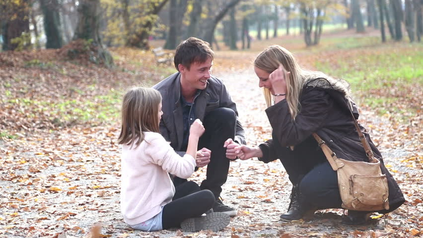 Attractive young parents having fun with cute daughter playing games in the park - HD stock video clip