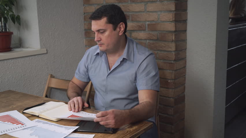 Manager man checks the sales data for the month and makes notes in a diary on the table are charts and graphs, middle-aged man. Soft panorama - HD stock video clip
