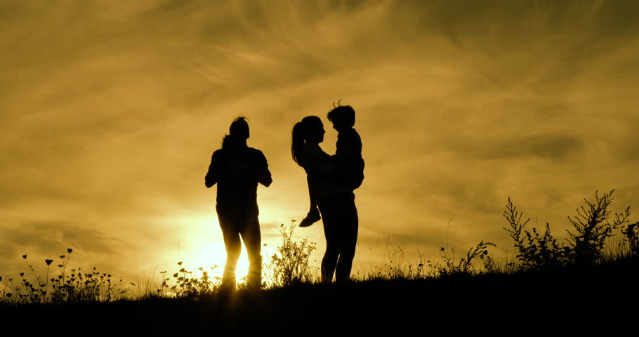 Happy family fun and hugs silhouetted dawn with orange sky | Shutterstock HD Video #15532423