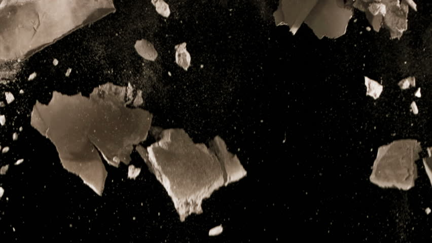 High quality motion animation representing various pieces of debris, falling in slow motion, on a black background.