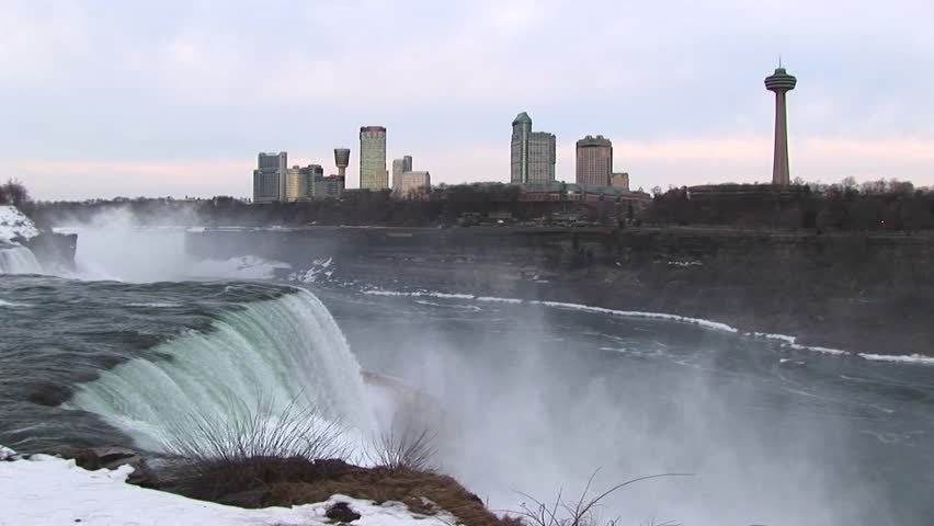 Wide shot of Niagara Falls in winter with tourist hotels in the distance