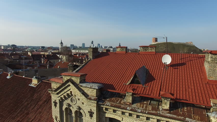 AERIAL. Smooth flight up above red roofs of houses in old town of Vilnius, the capital of Lithuania. Cathedral and Gediminas castle hill