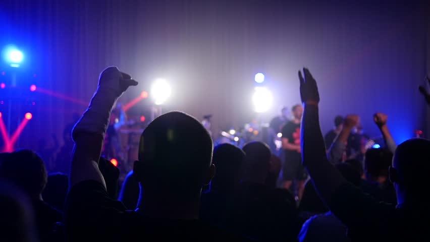 KHERSON, UKRAINE - MAR 26, 2016 - Free public music concert - Cheering silhouettes crowd fan spectators rais hands up in air enjoying concert - HD stock footage clip