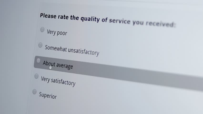 Macro shot of a mouse cursor on a monitor indicating a person giving a good or satisfactory service review on a computer based internet business customer satisfaction survey.