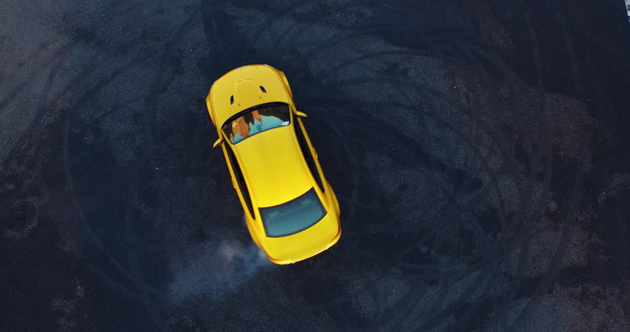 Top view of the golden car drifting on the road. ?ar makes a few laps. Shooting with a drone in 4k.  | Shutterstock HD Video #15627949